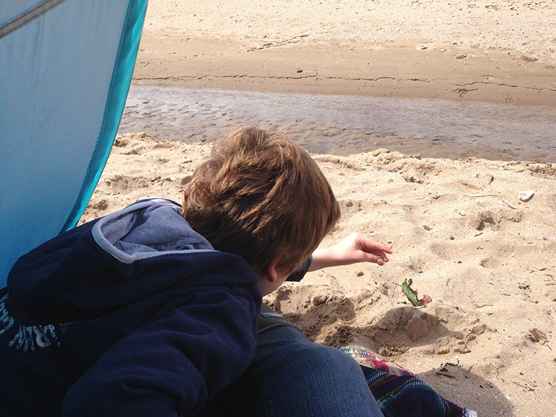 Protected by his pop-up tent, Connor feels safe enough to reach out and start exploring the sand.
