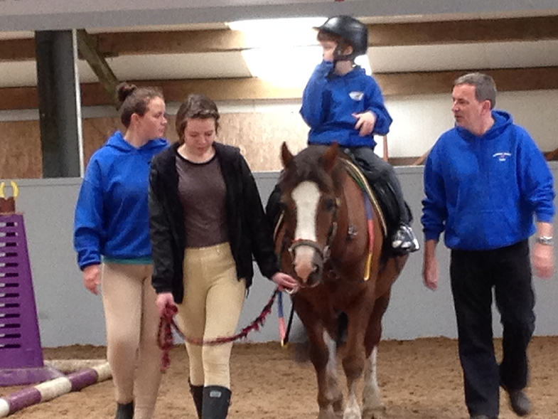 Now, whilst Connor still needs supervision, he is able to ride without being physically supported, with beautiful posture, pressing his feet into the stirrups, and sometimes (when not dancing) holding onto the saddle.