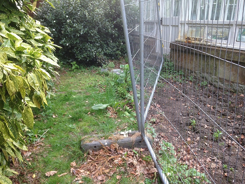 The actual fence, and concrete 'foot' both boys tripped over.