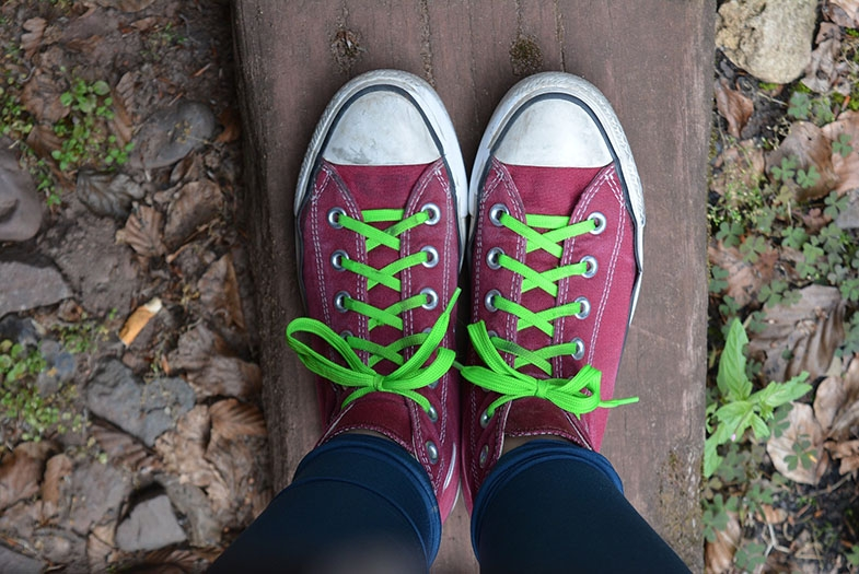 Photograph os a pair of dark red plimsoles with bright green laces.
