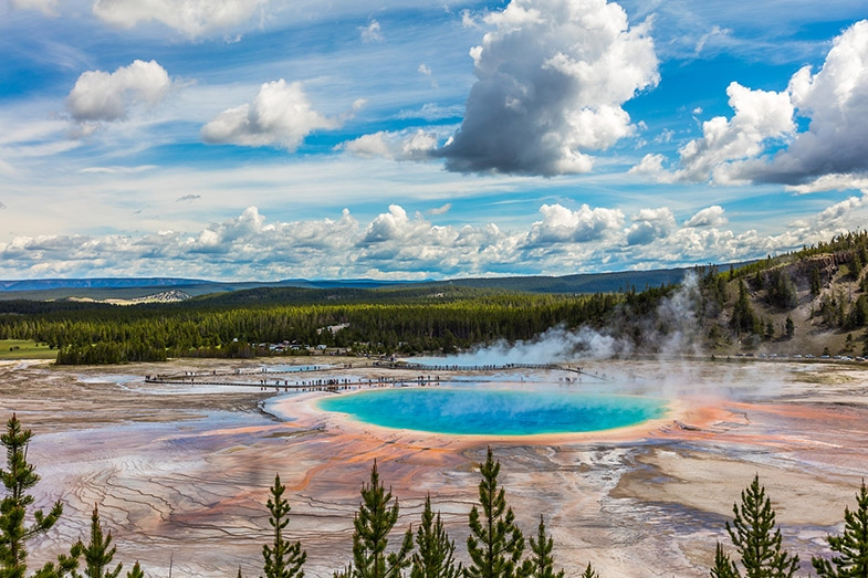 Photograph of Yellowstone National Park with blue pool of steaming  water.